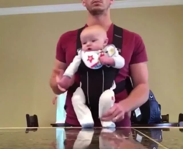baby was helped by his father to dance to music in living room