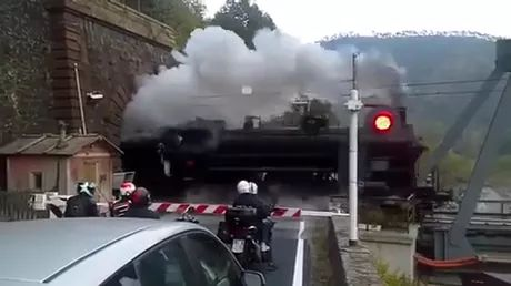 Cars and motorbikes are waiting for train to pass through tunnel