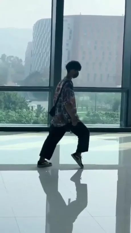 a man performs dance on the smooth background of building