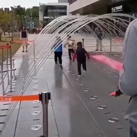 children try to run very fast through fountain to not get wet