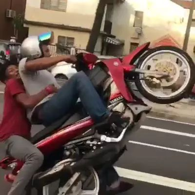 Two men perform driving a motorbike with a wheel on the street