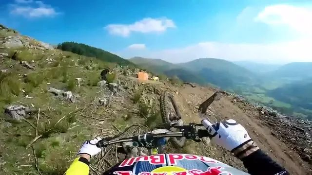 Racer riding sports bike from top of mountain
