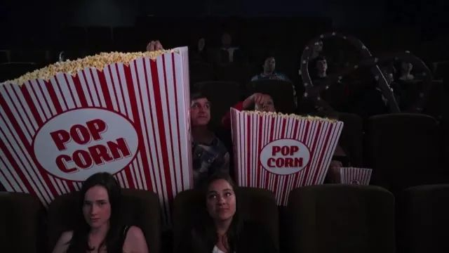 In cinema, family is watching movies with giant popcorn bags
