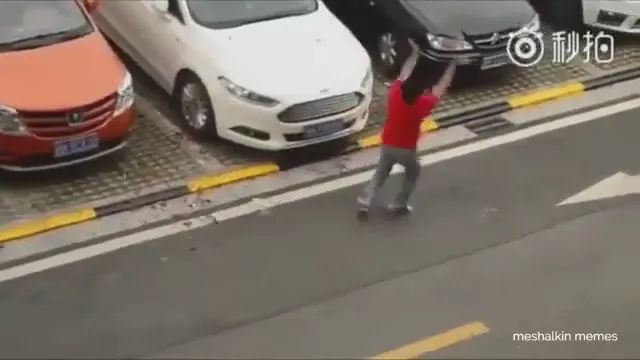 a man plays with wind next to parking lot