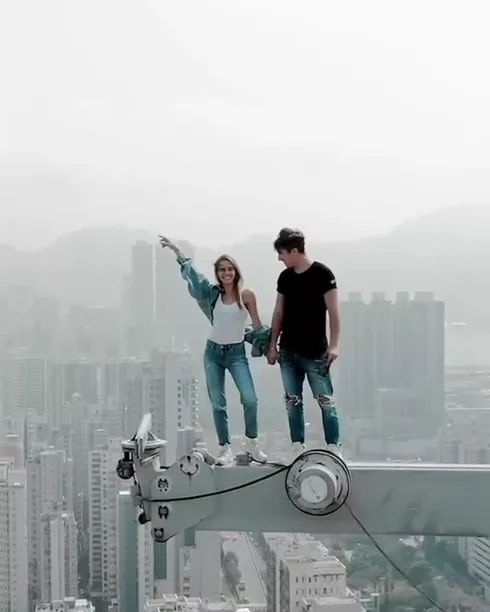 girl felt very satisfied when she was on the roof of a high-rise building.