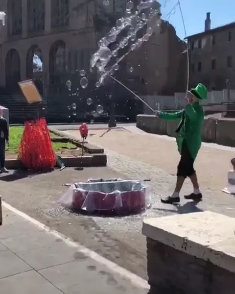 Tourists are using smartphones to record man playing with soap bubbles