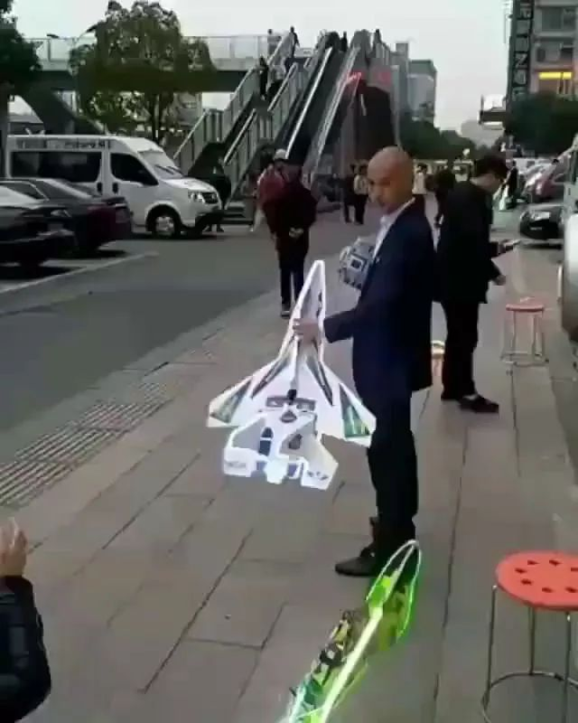 In street, a man launches toy plane into air