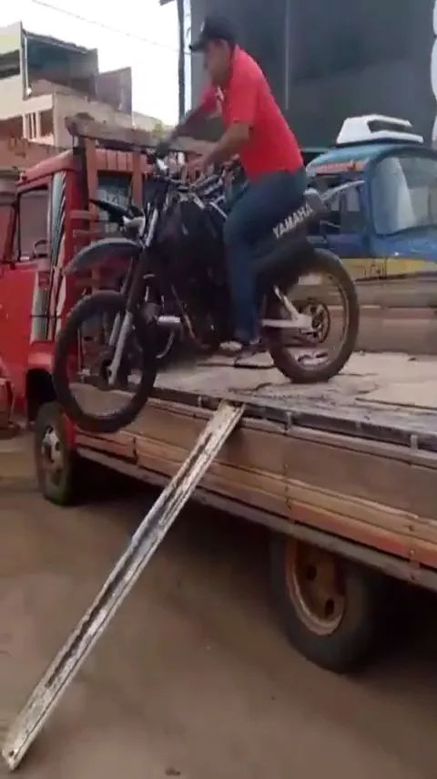 a man sits on a terrain motorcycle, moving from a tractor truck to ground - Video & GIFs | man, driver, terrain motorcycle, sports motorcycle, moving, tractor truck