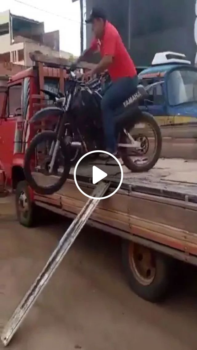 a man sits on a terrain motorcycle, moving from a tractor truck to ground