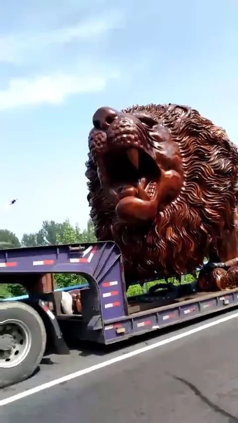 on the street, tractor truck is transporting huge wooden lion