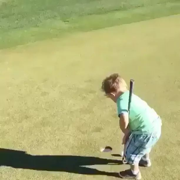 child tries to use a golf club to hit ball in hole