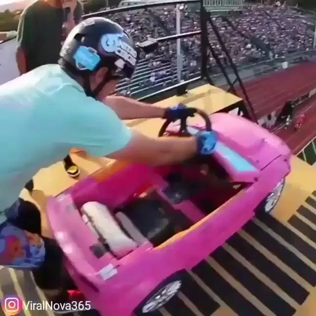 Camera with helmet, man driving a plastic toy car running down high slope