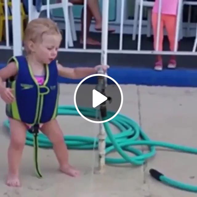 baby tries to use tap on the beach