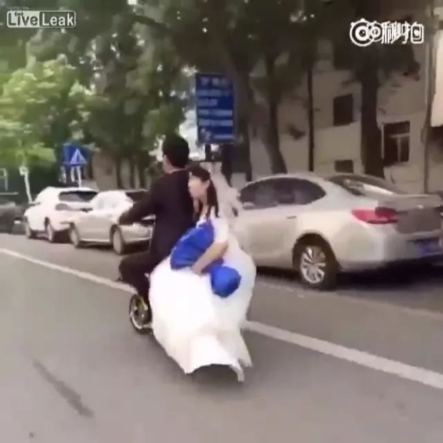 Groom and bride on electric bike in Chinese street