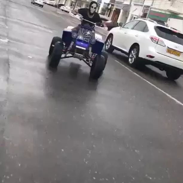 Man driving a four-wheeled motorbike spinning on the street