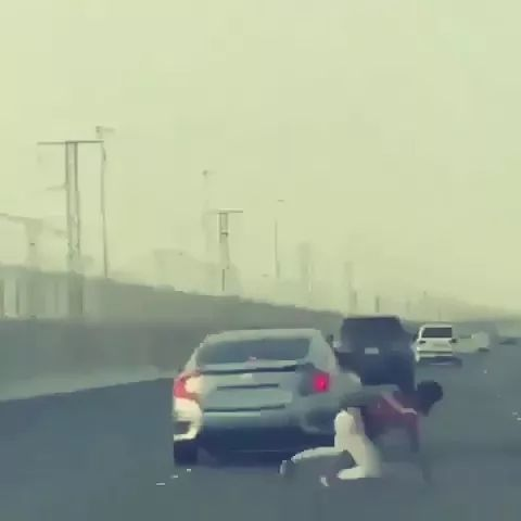 a man rushes out to car while car is running on the street
