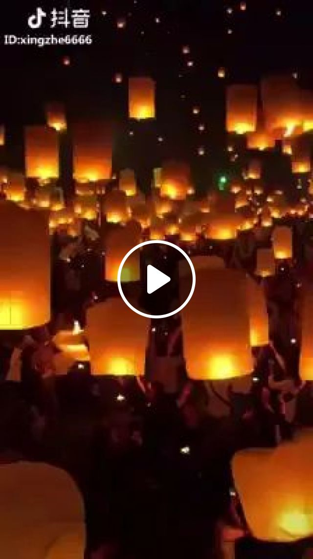 Thais gather along a river in Bangkok, and release handmade flower lanterns adorned with candles