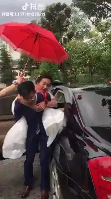 groom carries bride out of luxury car.