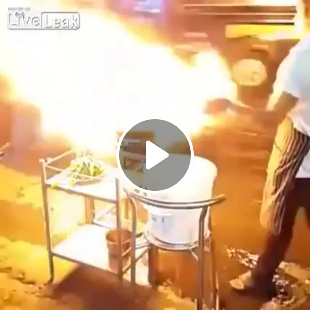 Traveling Thailand, chefs cook on the street a lot of cars pass by