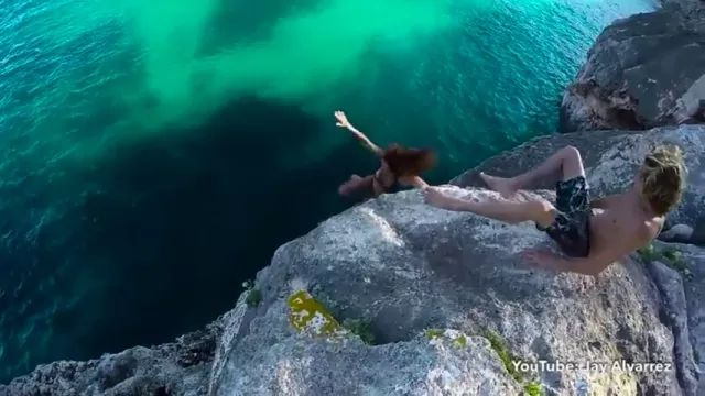 man helping girl jump from cliff to sea in travel
