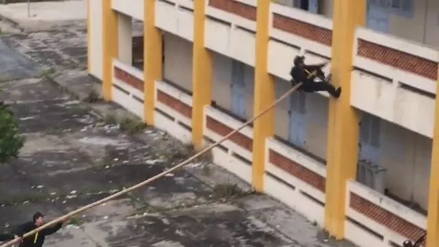 soldier climbed building with long wooden sticks