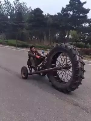 on the street, man controls a motorbike with a giant front wheel