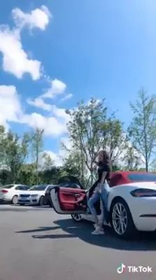 Girl taking photos next to sports car with her smartphone