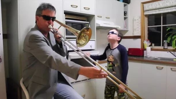 Father and son are performing music in kitchen