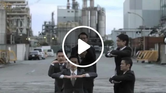 Men with fashionable clothes performing dance in front of power factory