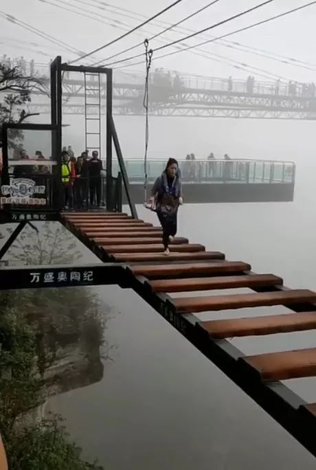Girl and challenges cross bridge on the top of mountain in China