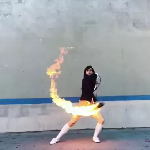 girl performs with a ball of fire