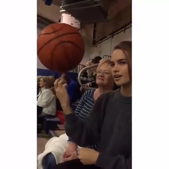 While watching basketball, girl turned basketball ball on her finger