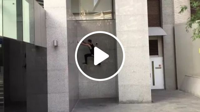 Man performs climbing wall of building
