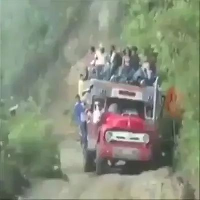 Truck driver carrying many people, passing through stream